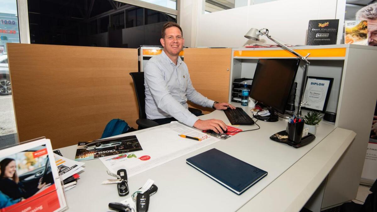 Bak skrivebordet hos sin nye arbeidsgiver er arendalsmannen i ferd med å gjennomføre sitt første salg.