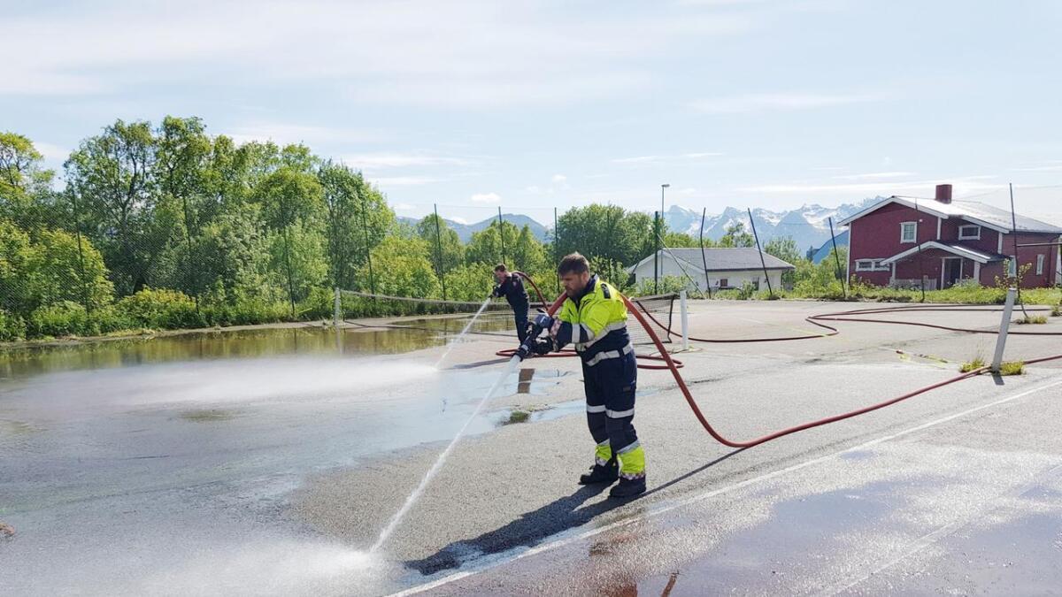 Ståle Rasmussen og Jan Roar Johannessen i Sortland brann og redning vasker tennisbanen på Sortland.
