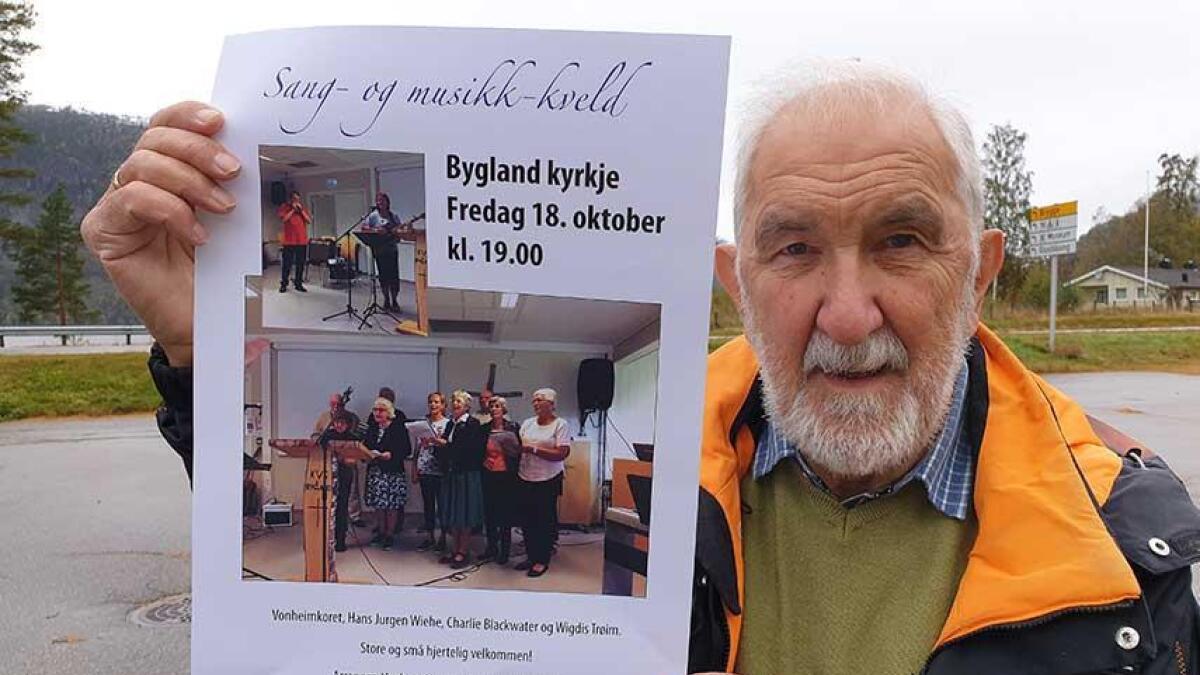 Harry Andersen med plakaten som fortel om konserten i Bygland kyrkje førstkomande fredag. Då blir det alt frå munnspel og orgel til Vonheimkoret.