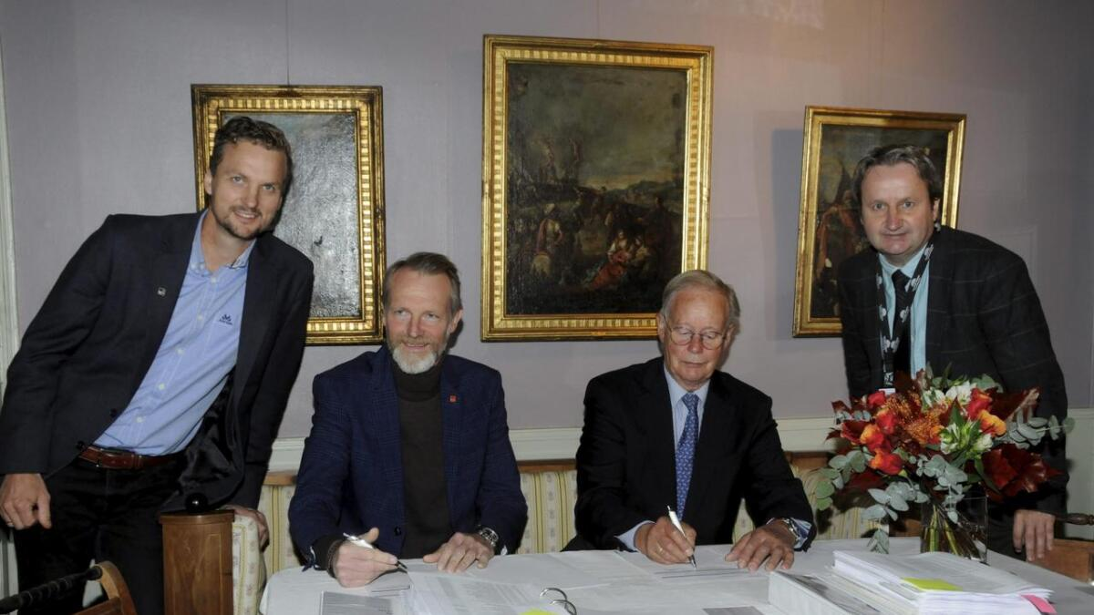 Med signeringspenn distriktsleder Lars N. Hjertås fra Veidekke Bygg Telemark/Vestfold (t.v.) og Lars Skjelbred, styreleder for Telemark Museum. På flankene Veidekkes prosjektleder Sondre Thorsen (t.v.) og museets prosjektleder Bjørn Rudborg.