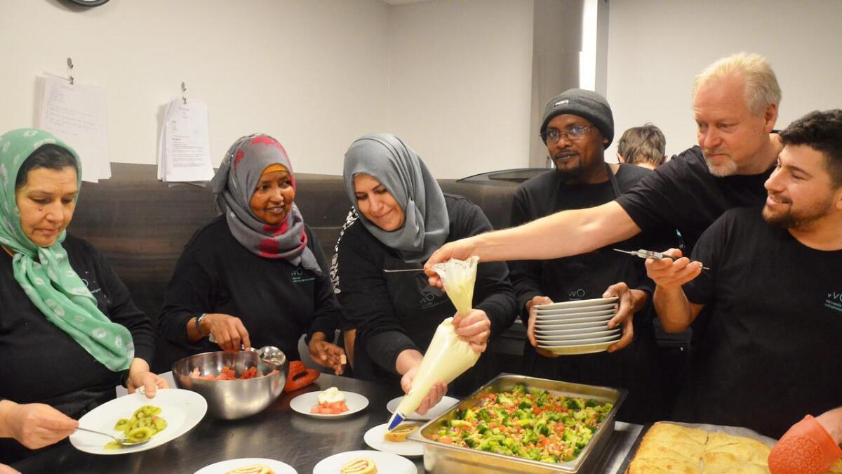 Kokk og lærer Ove Aasen har full trøkk på undervisningen i det lunsjen skal sereveres. Her instruerer han Geni Dahir Muhumed og Tsighe Habte som lager dessert mens de andre forbereder varmretten. Alle