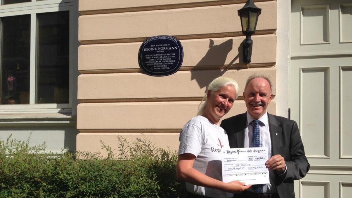 Skiltet er avduket i Stensgaten 3 i Sankthanshaugen, og ordfører Sture Pedersen får overrakt en symbolsk sjekk av Dörte Giebel som tegn på at 14.000 kroner står til disposisjon for å sette opp et blått merkeskilt i Bø (privat foto).