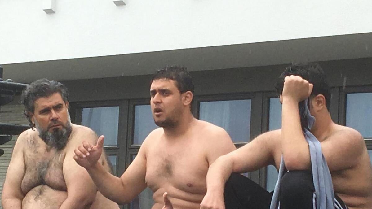Faren, Mohamad (f.v.) og sønene Ahmed og Fahad kledde av seg for å få merksemd om protesten. Mora, Walida, sat også i rådhustrappa fredag.