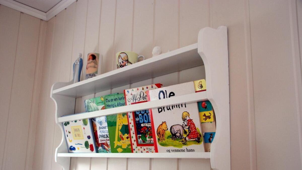 Gjenbruk. Denne hylla ble før brukt til asjetter. Austad har malt den, og hylla blir nå brukt til å holde barnebøker og leker.