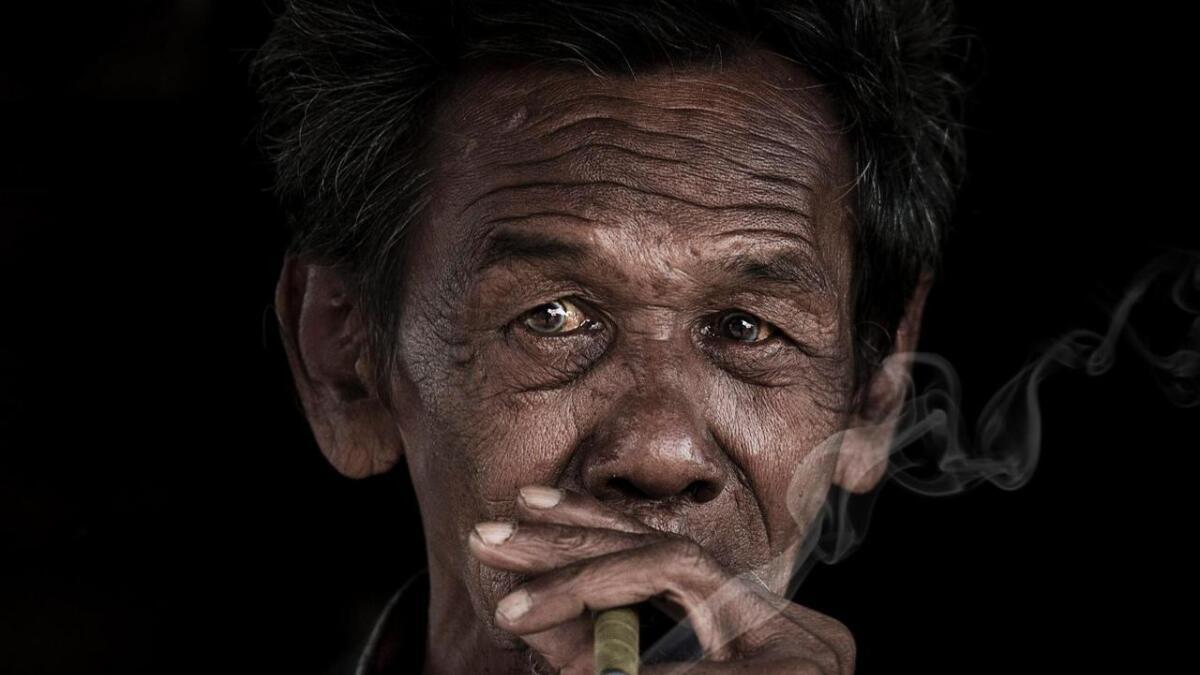 Denne mannen tok seg nokre drag i eit skur ved kanten av Mont Popa som ligg midt i landet. Det blir stadig fleire eldre i Myanmar, men ingen veit kor mange dei er. Familiane tek hand om dei fleste, etter buddhistisk tradisjon.