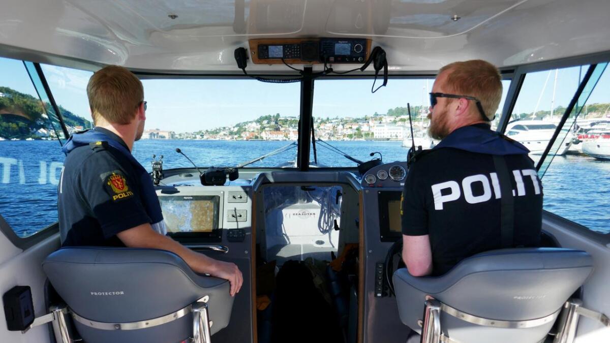 Jens Kristoffer Viken (t.v.) og Jens magne Hansen patruljerer med politibåten i Arendal.