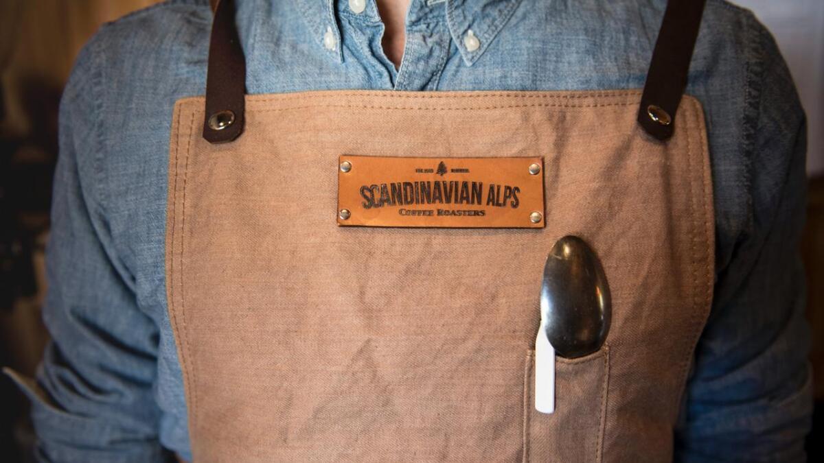 Arbeidsuniformen består av eit forkle med penn og matskei.