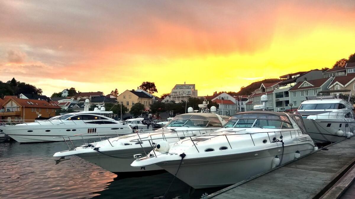 Grimstad er ikke det verste stedet å ta en bryggesleng en mild julikveld. Tirsdag var det som om solnedgangen satte fyr på himmelen over byen.