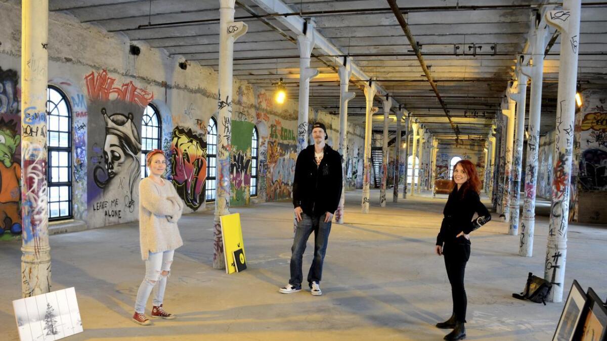 Kunstgarasjen har fått lov av Steinar Moe Eiendom til å ha  utstilling i PM5 på Smieøya. 31. Mai til 1.juni steller de i stand sin tredje popup utstilling i Skien. Fra venstreChristina Johansen, Tom Erik Nykås og Ingunn Rønjom. Ørjan Madsen og Olaf Sagen (ikke på bildet) bidrar også til utstillingen.