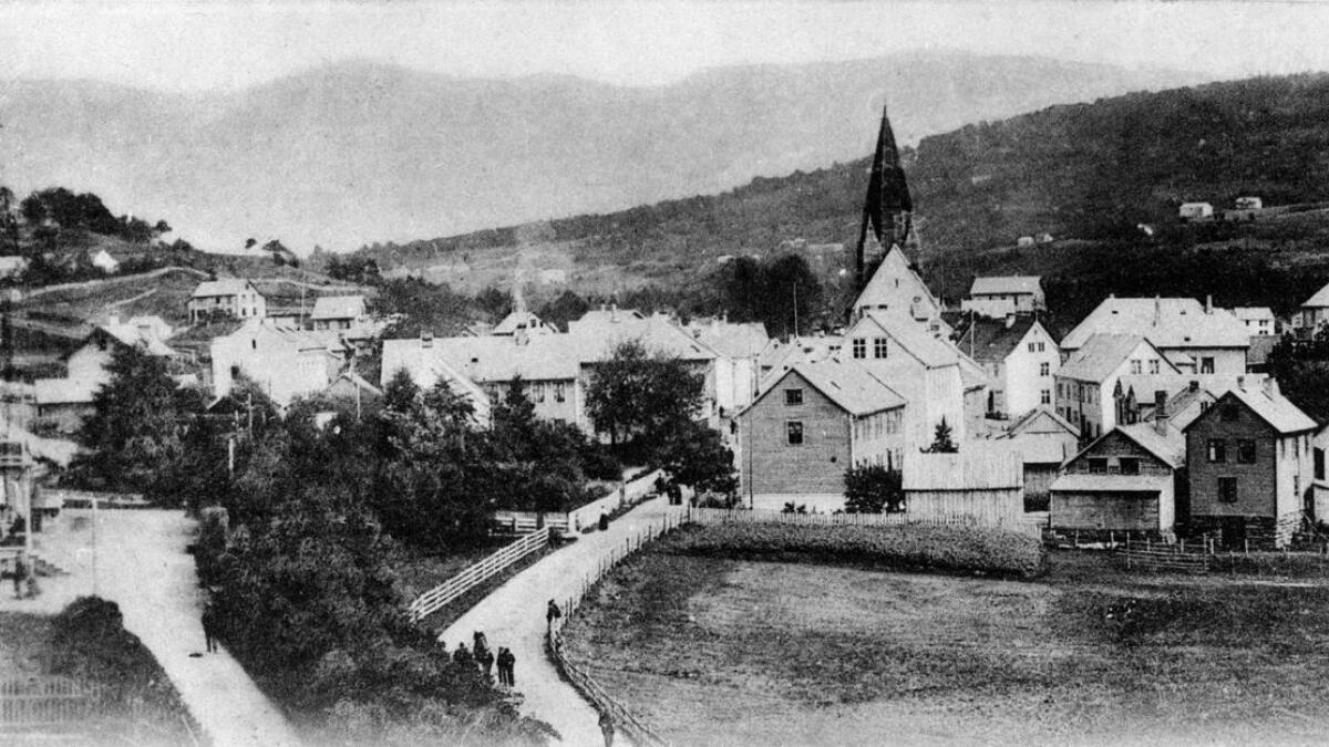 Artikkelen Gjæstgivere paa Voss er illustrert med dette fotoet av Vangen sett frå vest kring 1890. Skjenkestova Skrumpen låg like bak dei to husa til høgre i biletet.