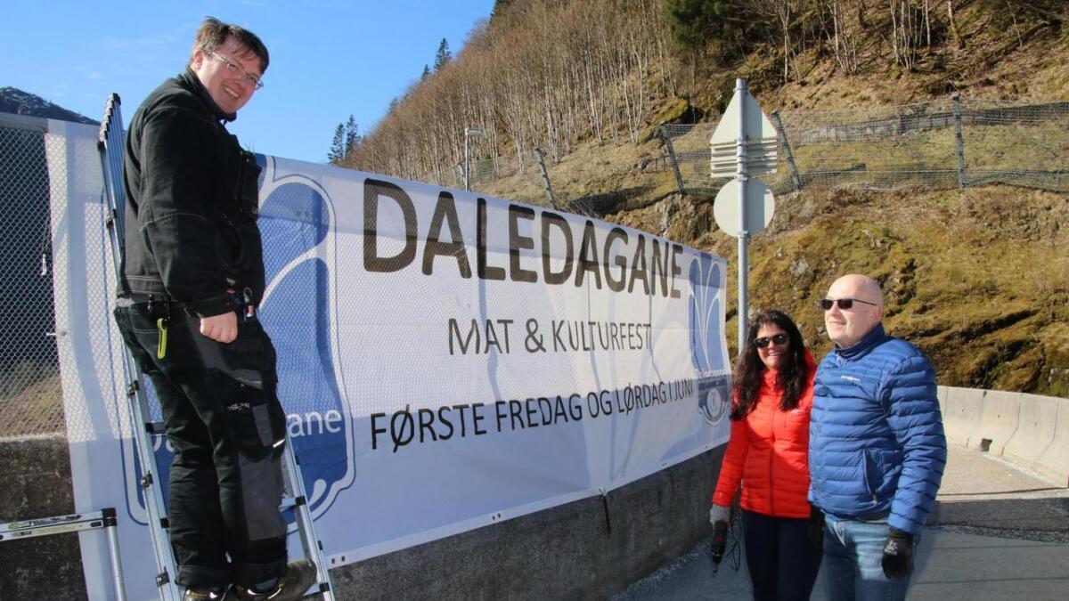 (F.v.) Boris Groth, Evy Kvamme og Ole Hesjedal i Daledagskomiteen hengjer opp banneret som skal minna folk om at Daledagane er 31. mai og 1. juni.