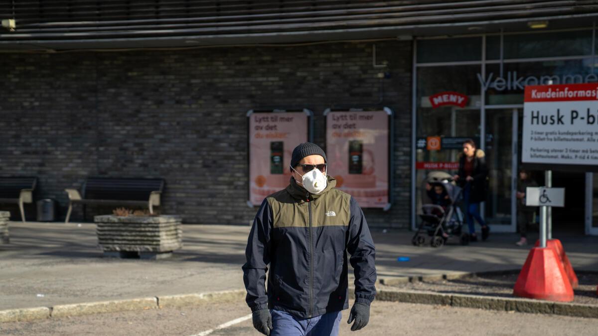 En mann beskytter seg mot smitte ved bruk av munnbind og engangshansker. Illustrasjonsfoto: Thomas Brun / NTB scanpix