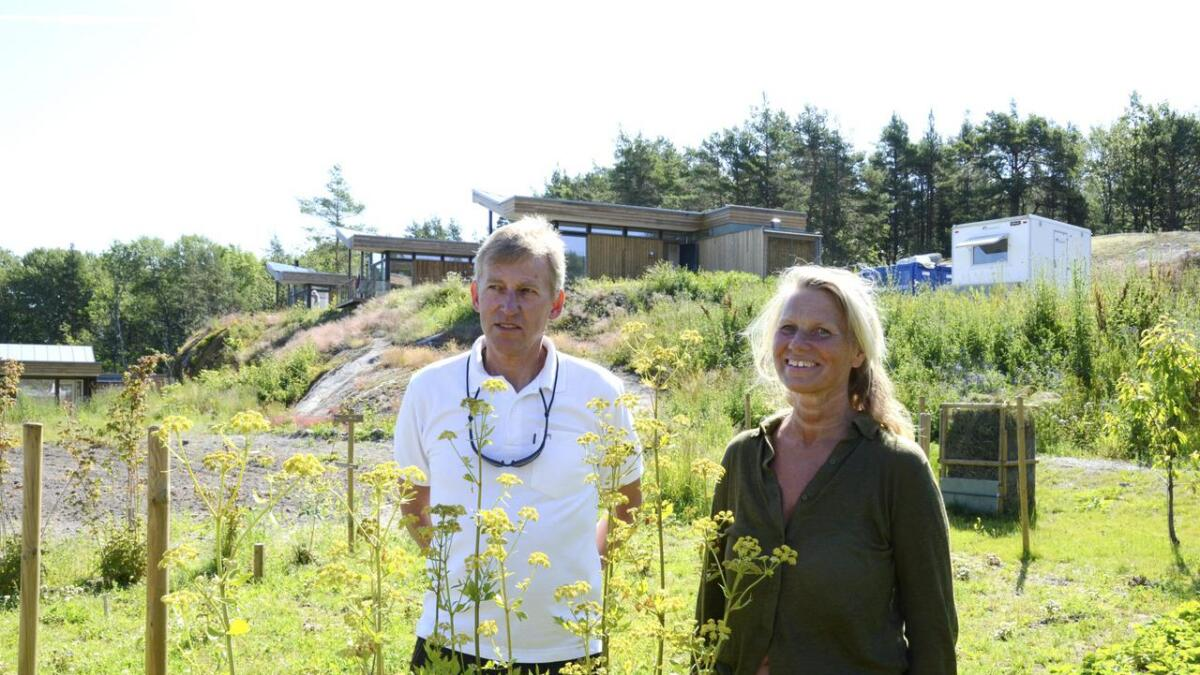 Hyttekolonien på Skåtøy har allerede fått tilflyttere, og det er grunneier Bjørn Halvorsen glad for. Her står han i sin egen åkerlapp sammen med en av arktaktene i Snøhetta, Margit Tidemand Ruud, som var med på å tegne ut hyttene.