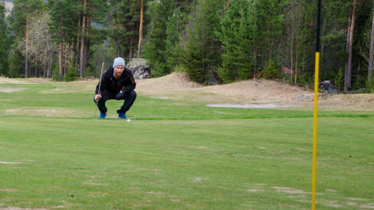 Stein Thøger Vindegg set seg på huk og vurderer kurven på greenen under sesongdebuten på Granheim.