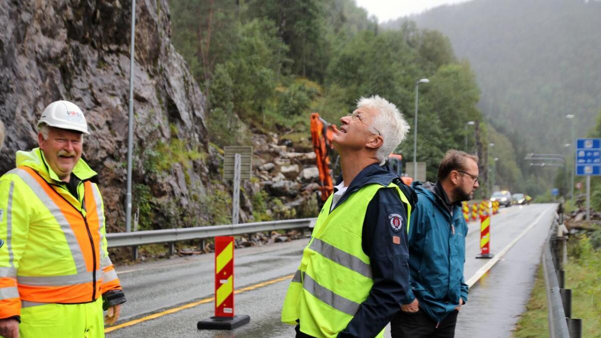 Jon Askeland (midten) kjende seg ikkje trygg på rasstaden ved bompengestasjonen på Bolstad. Til høgre står Vidar Skeie og ser ned på kampesteinane som har dundra ned i fjorden. Trafikkdirigent og styreleiar i Vossaløysinga, Einar Larsen (til venstre) er litt meir van med omgjevnadene.
