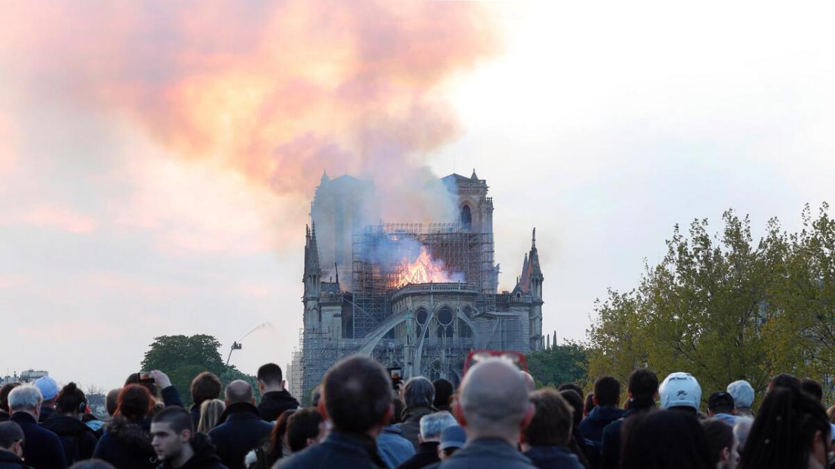 En folkemengde følger slukningsarbeidene rundt den brannherjede katedralen.