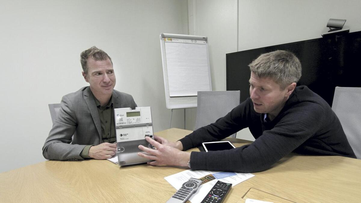 Michael Rapp og Kjell Løyland med den nye måleren som du snart får installert i hjemmet ditt, om den ikke er på plass allerede. Løyland peker på et lite kontaktpunkt der man kan kople til en kabel og selv overvåke eget strømforbruk.