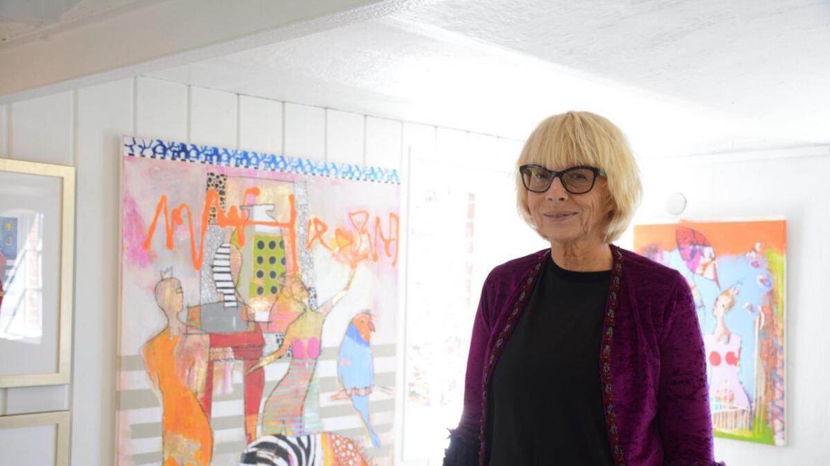 Anne Valen Næss kunst kjennetegnes av fargesprakende malerier. I bakgrunnen er maleriet hennes «Drømmen om en bauta».