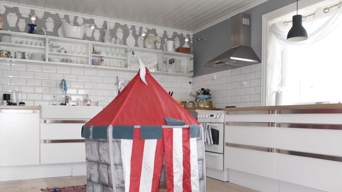 Mens Karine lager mat leker ungene på kjøkkengulvet.