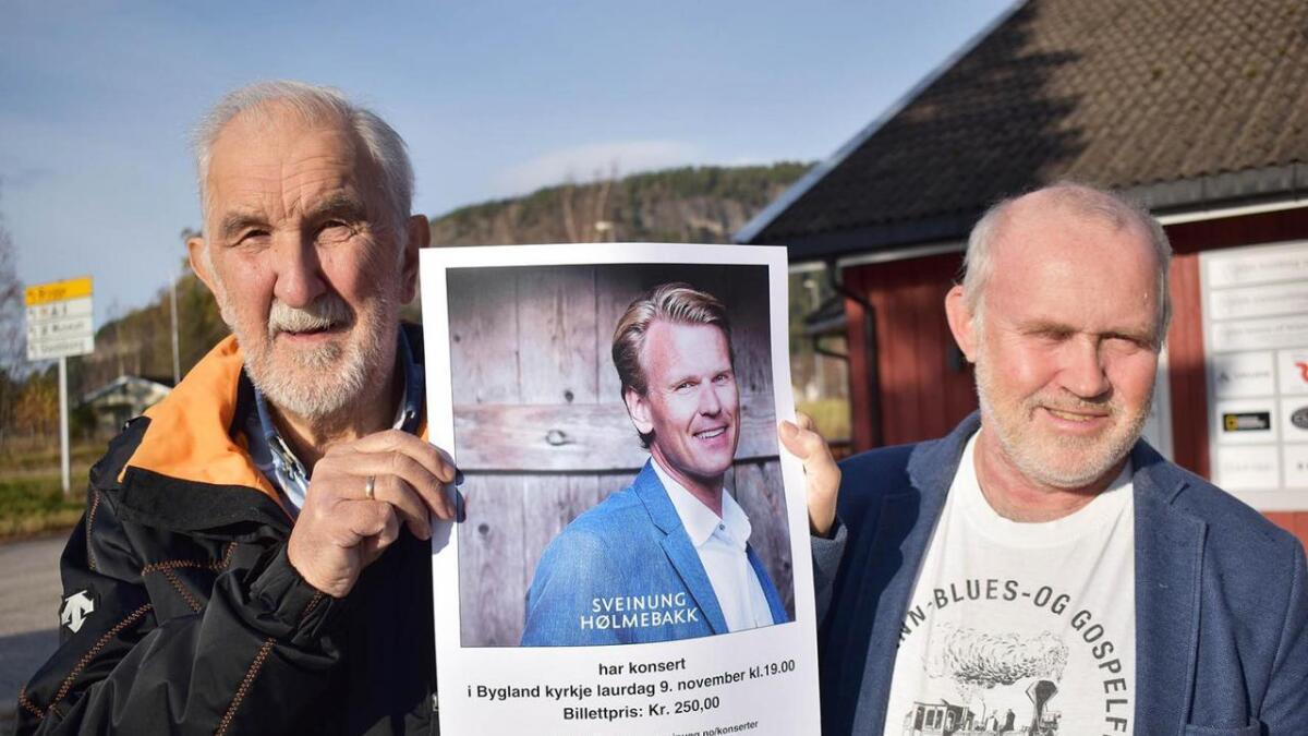 Harry Andersen (t.v.) og Olav Nilsen med plakat som fortel om Sveinung Hølmebakk sin konsert i Bygland kyrkje førstkomande laurdag.
