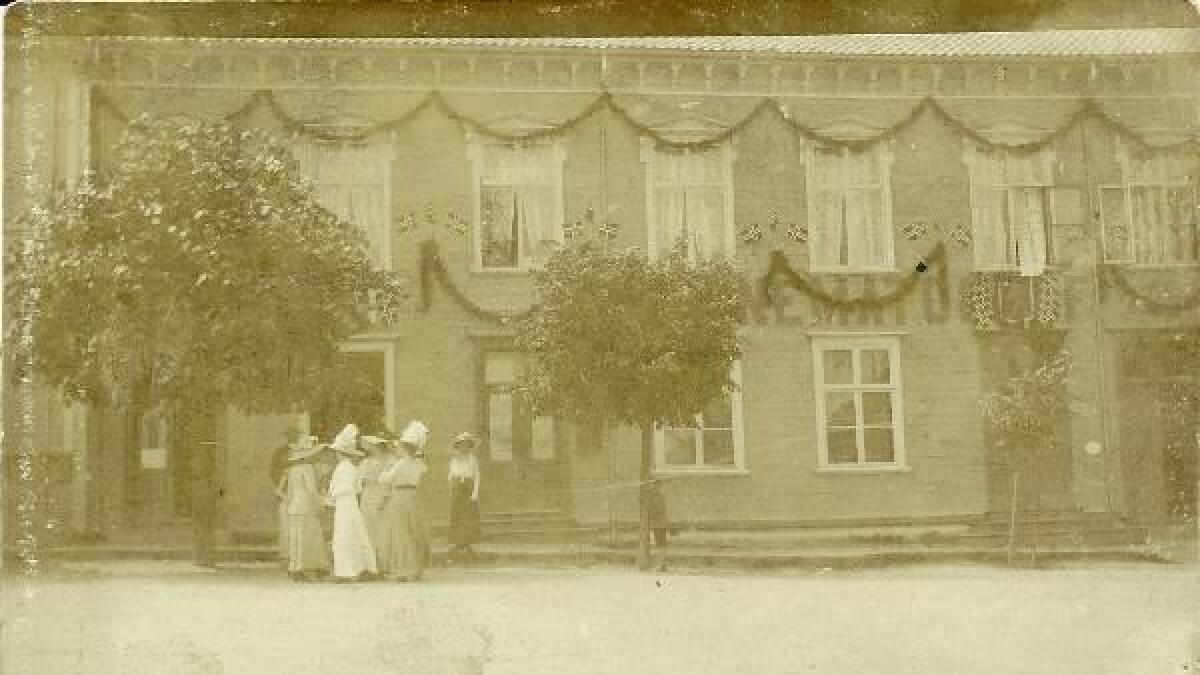 På veggen kan en skimte noen av bokstavene i KINEMATOGRAF. Denne første kinoen var i doktor Scheens gård på Torvet, der som Sparebanken Sør holder til i nå.  Bilde fra boka.
