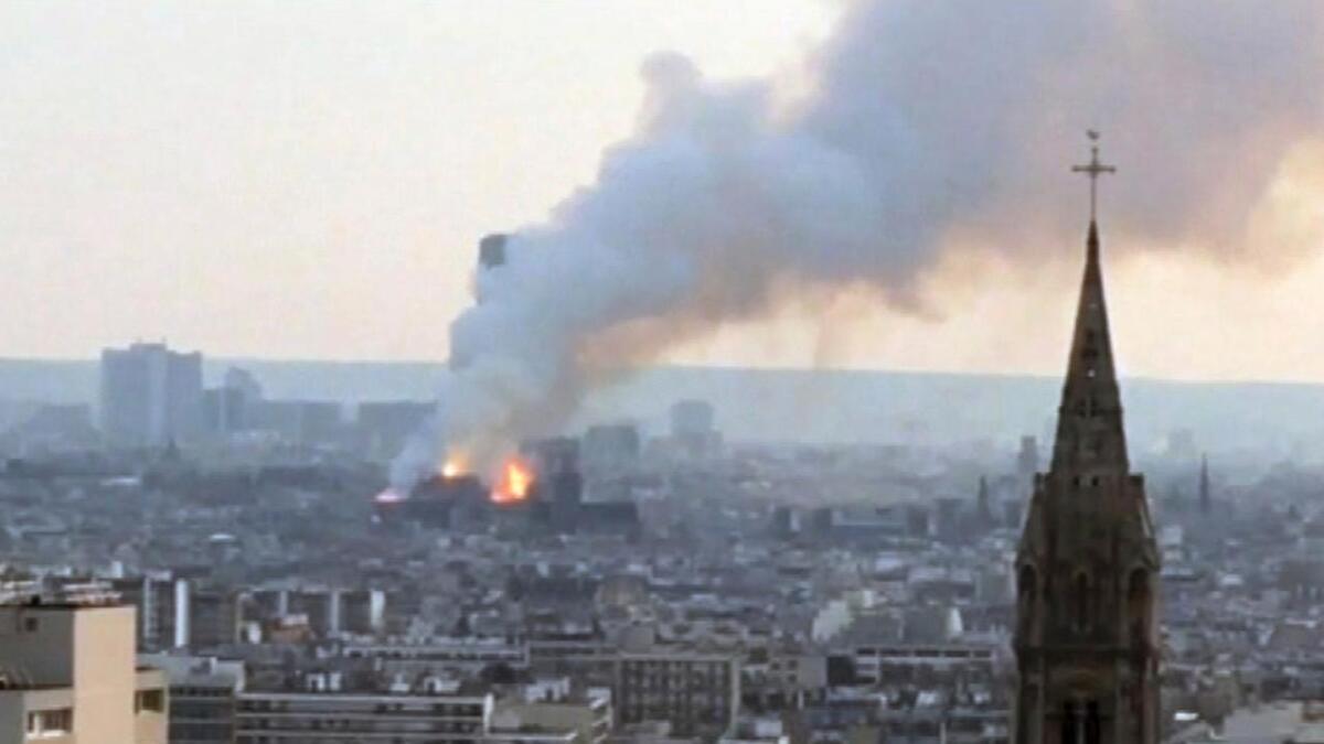 Tykk røyk stiger mot himmelen fra Notre-Dame-katedralen i Paris.