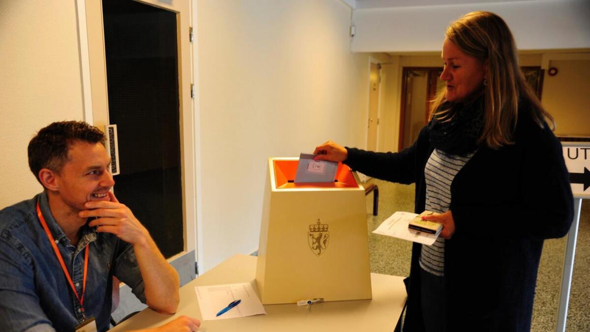 Lise Steinbråten puttar stemmesetelen i urna som valfunksjonær Stian Røstberg passar godt på.