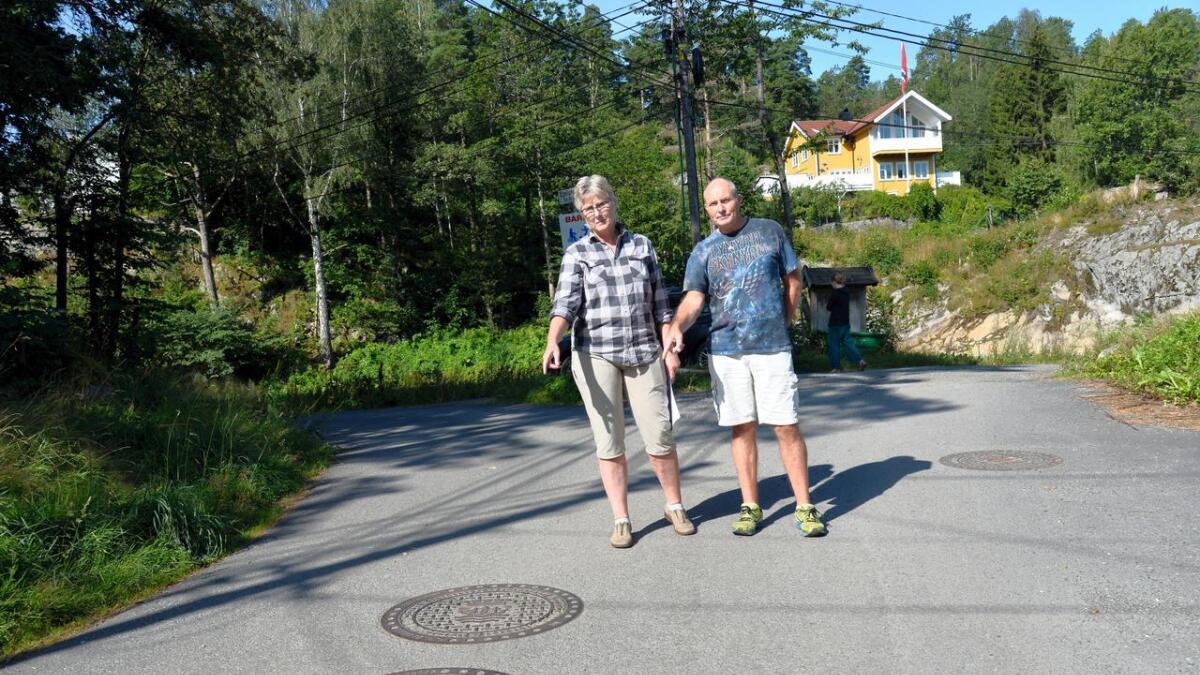 Rita og Tore Lunde viser kummene hvor det kommunale anlegget stopper. Egelundveien fortsetter bak dem, men der er den privat.