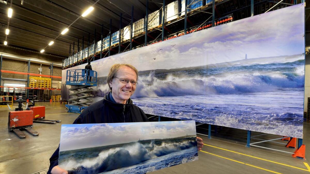 Fotograf Alf Georg Dannevig holder en liten versjon av kjempebildet på 80 kvadratmeter som nå pryder cola-reoler på Askos lager i Lillesand. Nå ser han et nytt marked for megastore bilder  på PVC-duk, montert utenpå stillaser, eller som her, på reoler ved Askos lager i Lillesand.