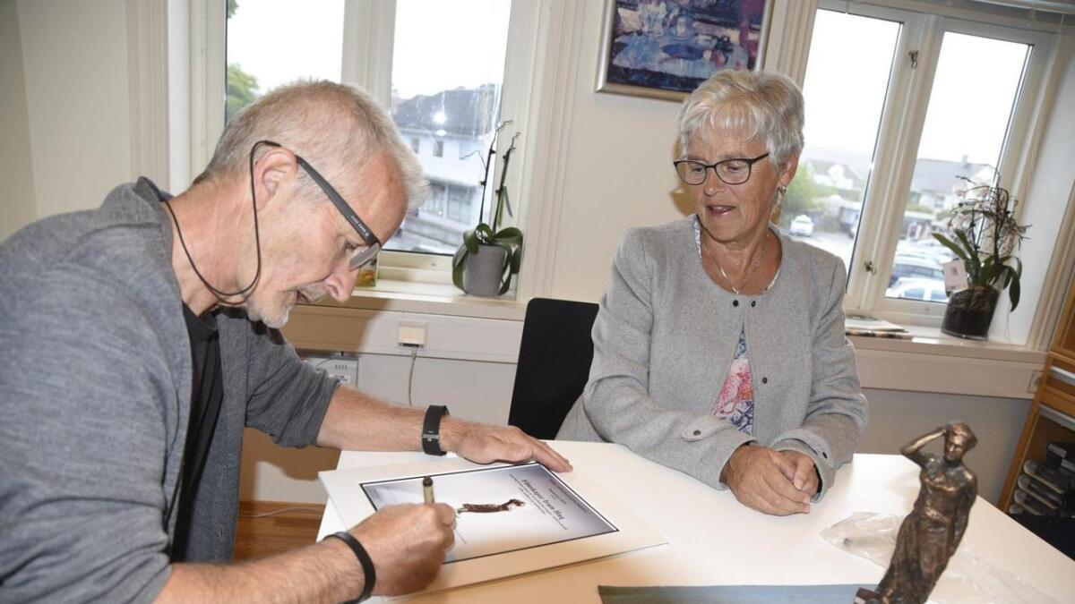 Ny styresekretær og fitjarbu Bjørn Haaland signerer diplomet saman med styreleiar Haldri Karin Engenes. Til høgre Torastatuetten laga av Os-skulptør Arne Mæland
