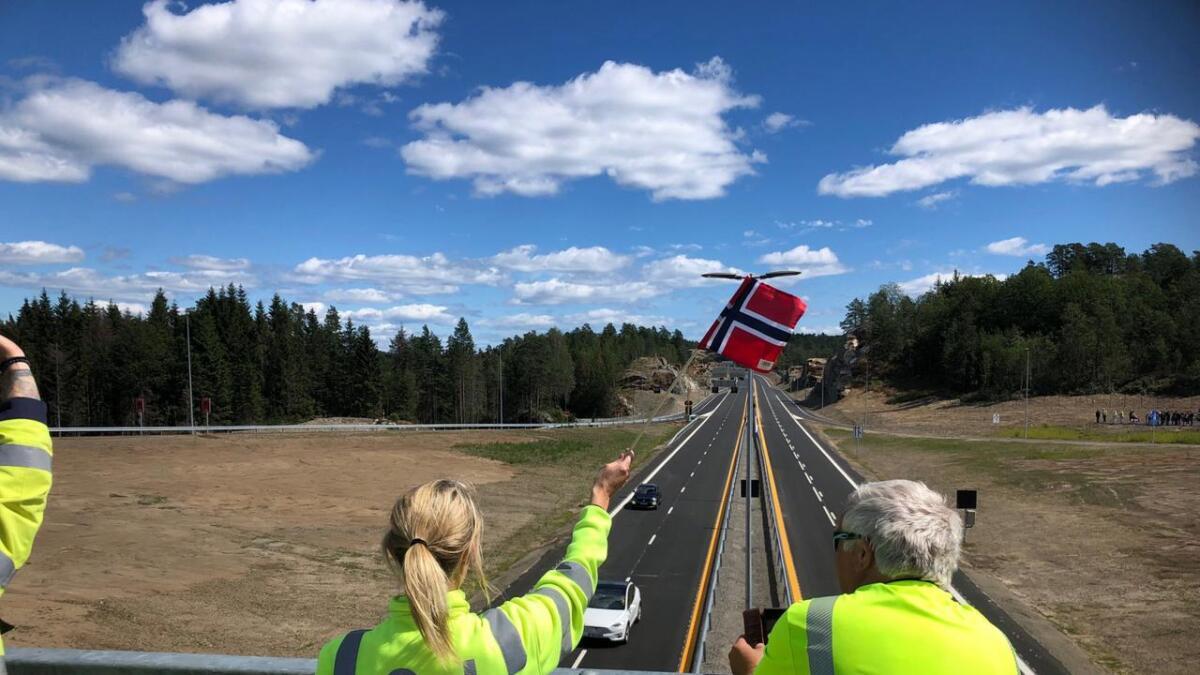 Nye Veier-ansatte flagget for bilene som kom først under Longum-brua fra øst da nye E18 åpnet 2. juli.