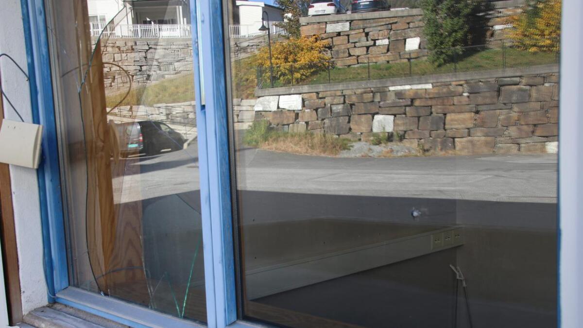 Midt i vindauga til høgre, er det hol etter eit skot. Vindauga til venstre er knust.