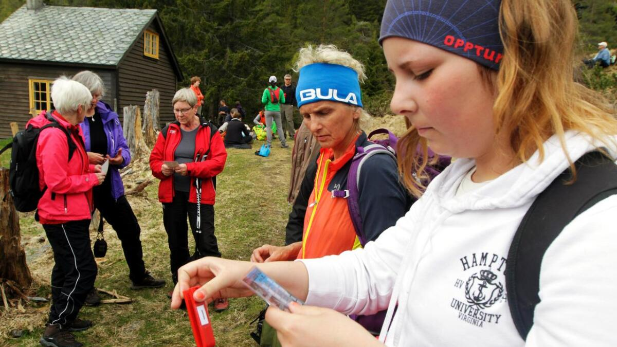 Tuva Vestrheim klipper merkje i stølskortet på stølen Vatnaset i Granvin sommaren 2015. Reidun Tveito ventar på tur.