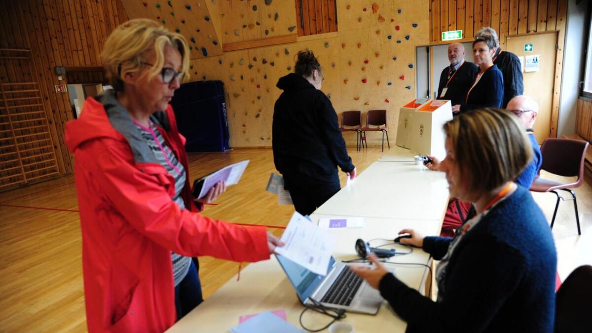 Valfunksjonær Anette Karterud kontrollerer valkortet til Karin Skrindo Granberg. Inger Marit Halvorsen er klar til å leggje stemmesetlane i urna. Valfunksjonærane Nils Ove Svensgård, Geir Tretterud, Anne Berit Jorde og Inge Ragnar Gåsterud kontrollerer.