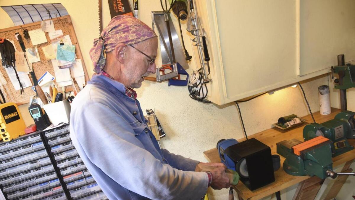 Til slutt blir stålet polert. Her står Jørgensen i verkstaden sin i kjellaren på bustadhuset og legg voks på poleringsmaskinen.