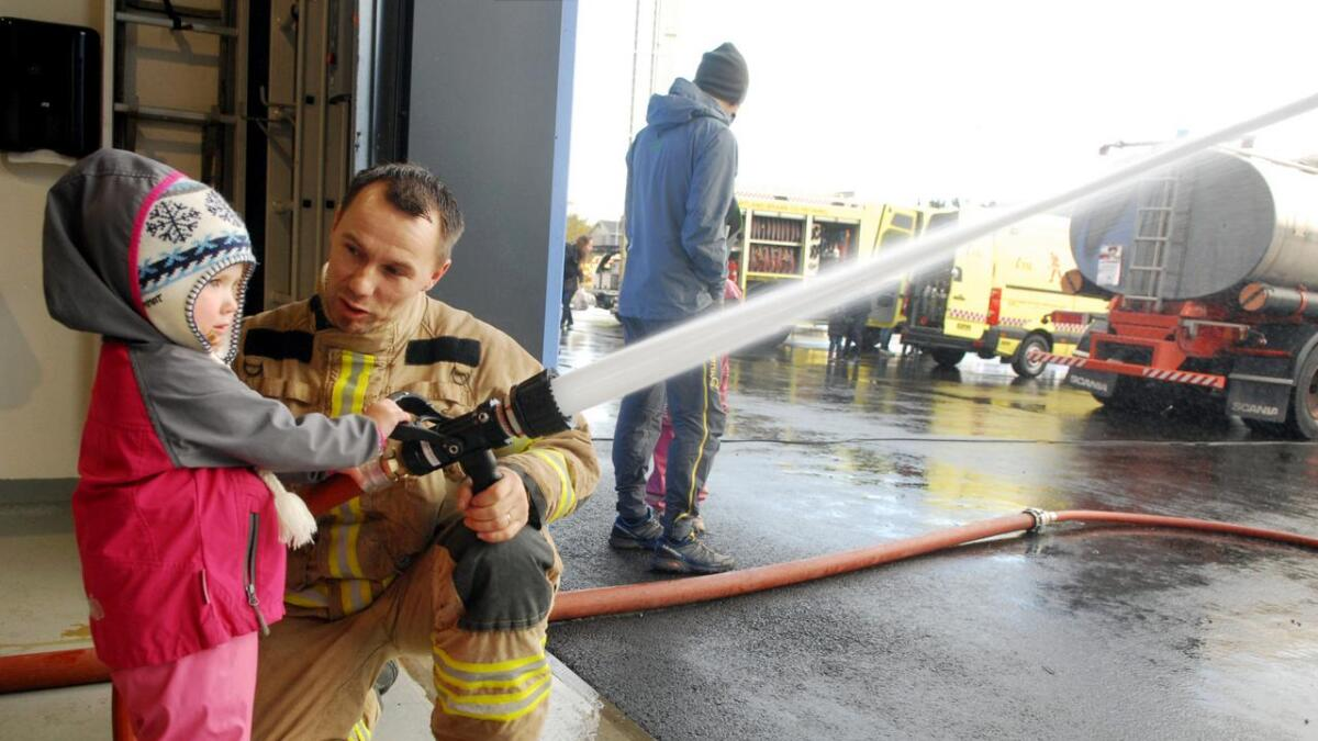 Sigrid Grandum Johnsen (3) fikk prøve å spyle med brannslangen, med god hjelp fra brannmann Kai Hansen. (Alle