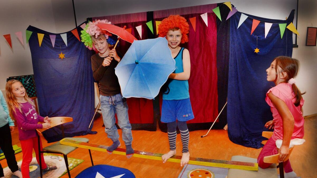 Oliam (7) og Filip (7) balanserer på planken og bytter paraplyer på midten. Til venstre passer Juliane (8) og til høyre Sulia Theres (9), på.