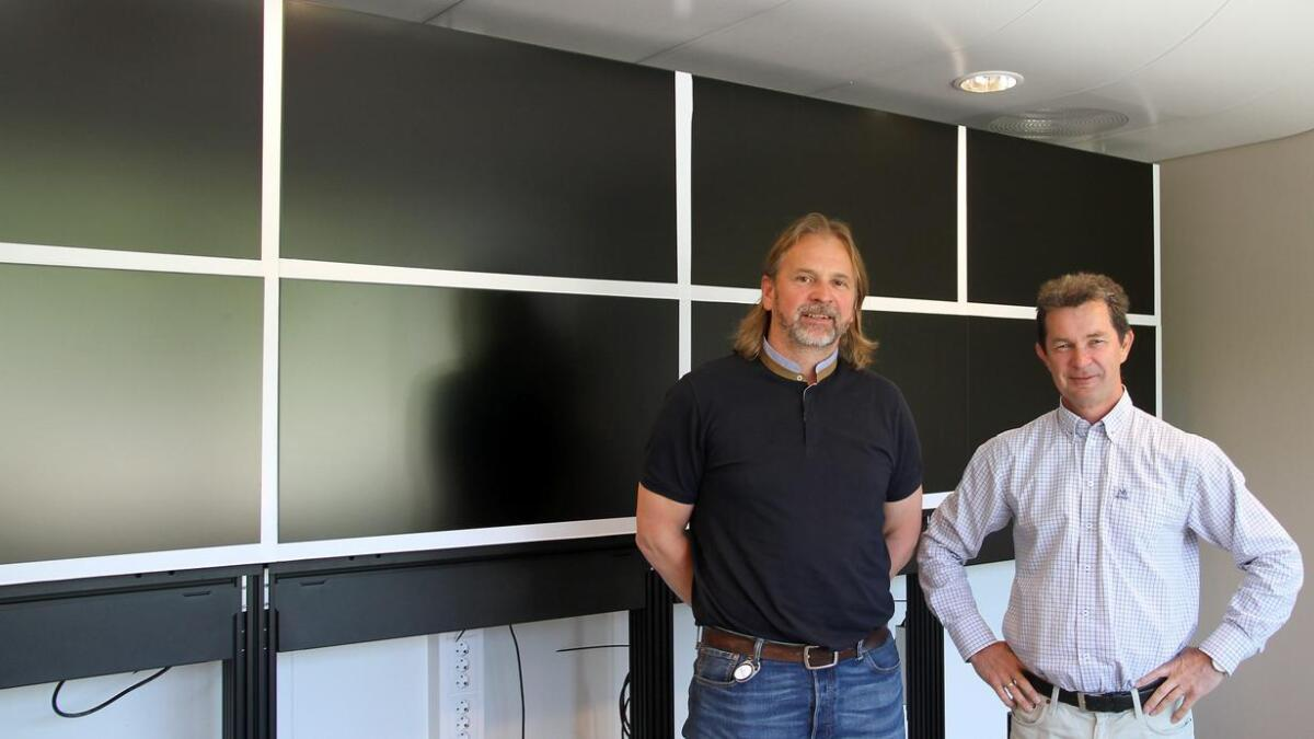 Markedssjef Bjørn Tång (t.v.) og daglig leder Asgeir Knutsen på datarommet, der en operatør kan overvåke industriprosesser over hele verden.
