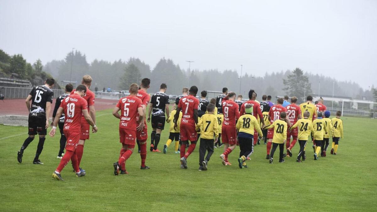 Unge Bremnes-spelarar følgjer Brann- og Sogndal-spelarane ut på grasmatta