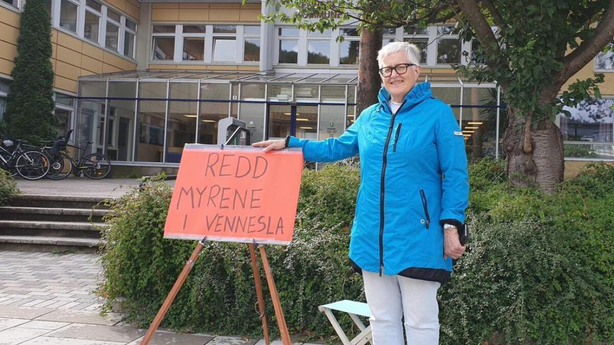 Anne Bergit Jørgensen står med plakat foran Herredshuset for å få hindre at det dyrkes på myrene i Vennesla.