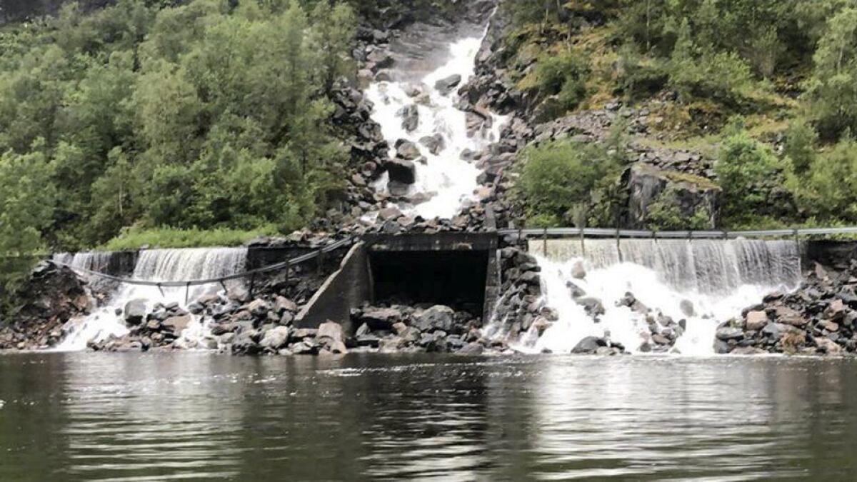 Jord og steinar har rasa ut, og elva har gått over vegbana fleire stader.
