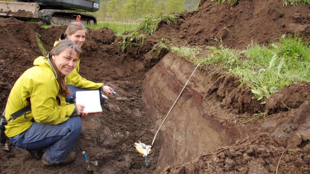 Geologene Kari Sletten og Paula Hilger undersøker jordlagene, og kan tydelig se at det har vært skred av sand ført via flom eller snø over torvlaget.