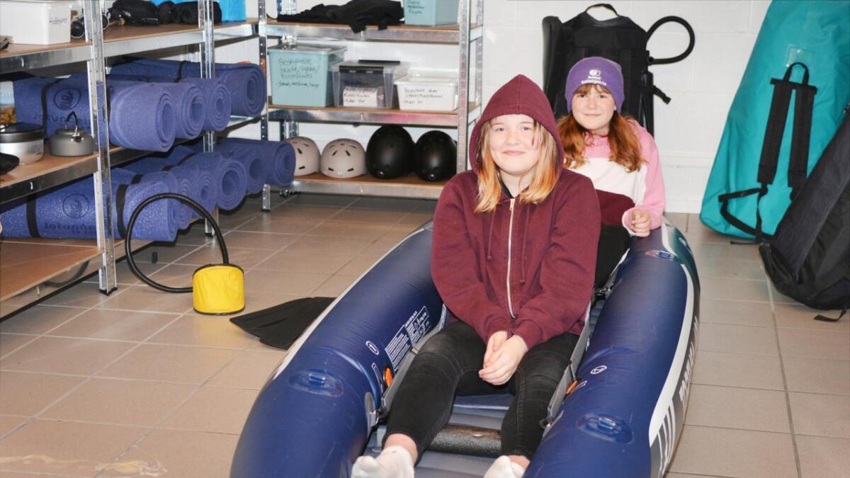 På bildet ser vi to glade jenter i en oppblåsbar kajakk, Aurora Holst og Vilde Margrethe Pettersen i utstyrssentralen i Servicebygget på Straume.