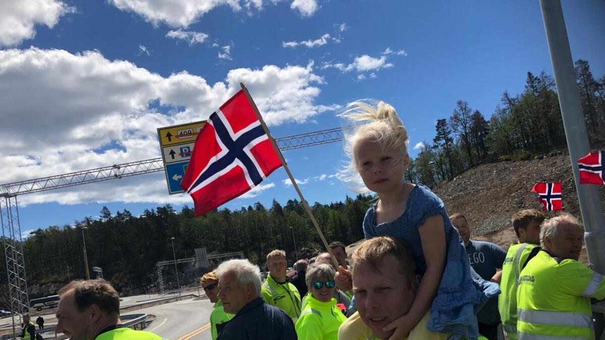 Sanna (4) viftet med flagget fra pappa Gjermund Hagas skuldre under åpningen. Gjermund fra Rygene jobber i NCC og har bidratt til legging av 300.000 tonn asfalt de siste to årene. Nå blir det noen måneder til her, men så vet han ikke hvor ferden videre går.