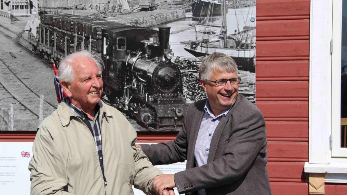 Odd Johansen, den siste gjenlevende i Lillesand som hadde sitt virke ved togstasjonen foran det nye skiltet, sammen med ordfører Arne Thomassen.