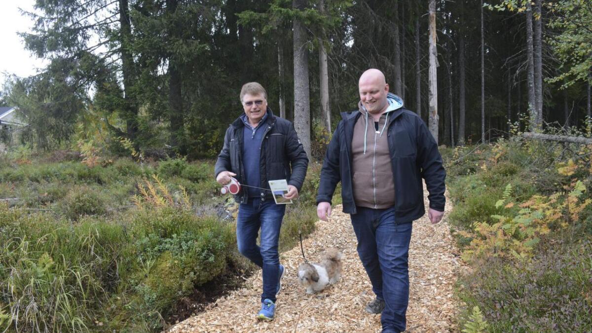Nestleder Gunnar Foseid (t.h.) og leder Terje Willy Gulbrandsen i Vestre Fenstad Vel går her på nylagt flis på en av de merkede stiene på Brårud. Hunden heter Pia.