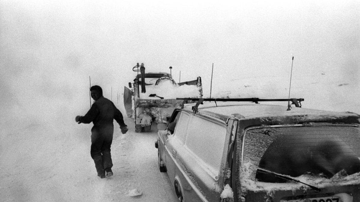 Ein bil står fast og må hjelpast laus av brøytebilen. Rv7 over Hardangervidda.