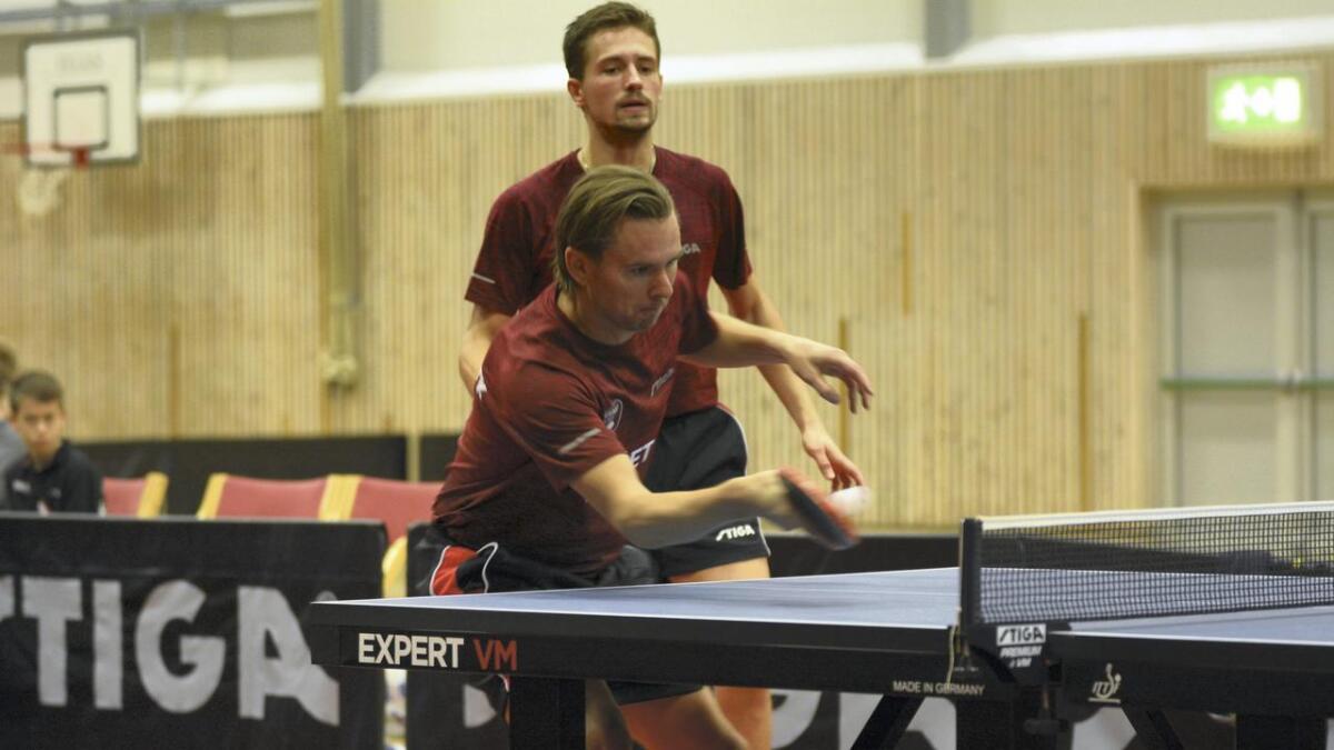Magnus Molin slår, medan Carl Ahlander følgjer med. Dei to botnsolide spelarane vann dobbelkampen sin mot Eiker med 3-0.