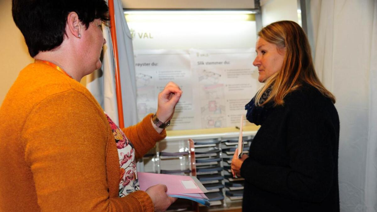 Valfunksjonær Åse Berit Lio forklarar Lise Steinbråten om listene til kommunevalet og Viken-valet før ho går inn i avlukket.