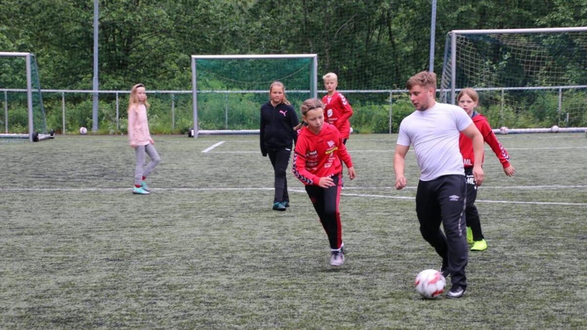 Instruktør Stian Lid Lervik spelar fotball med deltakarane på fotballskulen.